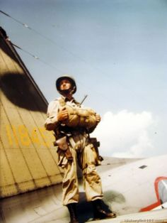An American soldier with parachute stands on the wing of a plane. Airborne Infantry Training Center.