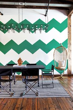 Fresh & eclectic global styled dining area. Love the green + white chevron feature wall & the hanging pod chair. Brilliant.