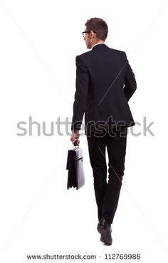 back view of a walking business man holding a briefcase and looking to his side…