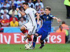 Mesut Özil de Alemania y Lucas Biglia de Argentina compiten por el balón.