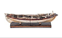 19th century bone and hardwood static model of a whaling boat, finely executed in bone and hardwood, with detailed fittings, fixtures and rigging, above a plinth base, the model 8 cm high, 27 cm long, 7.5 cm deep