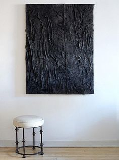 "An ultra-textured black painting by Alex Fideli hangs above a stool of Samuel's design. Even the backdrop brings dimensionality and rough-and-tumble texture: The floors were bleached and pickled to reflect more light, and the walls were plastered to be a little rough. Get more modern, masculine and minimalist interior design ideas and inspiration on ""Inside the Atmospheric Chelsea Pad of Ascending Design Star Samuel Amoia"" on the One Kings Lane Style Guide!"