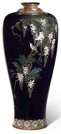 pair of cloisonné enamel vases By Ota Tameshiro, Meiji period (late 19th century) Both of baluster form with a slightly splayed foot, worked with silver wire and polychrome enamels on a dark blue ground with birds perched on trailing branches of wisteria, a floral lappet band at the foot and scrolling floral vines at the collar, with the Ota mark on the underside of both vases. Each 7 ½ in (19.1cm) high. Bonhams 2014 - $3750
