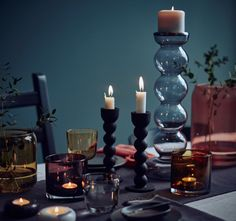A well-laid table with black candlesticks and tealight holders, vases and glasses in coloured glass.