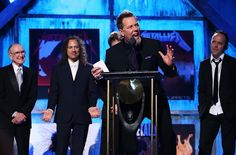 James Hetfield of Metallica speaks while Ray Burton, father of deceased bandmember Cliff Burton, Kirk Hammet, Jason Newsted and Lars Ulrich look on at the Annual Rock and Roll Hall of Fame. Heavy Metal Wedding, Metallica, Jason Newsted, Robert Trujillo, Kirk Hammett, James Hetfield, Social Platform, Rolling Stones, Megadeth