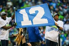 Seattle Seahawks player Kam Chancellor and Russell Wilson hoist a 12th Man flag after winning the NFC Championship against the Green Bay Packers. 1/18/15