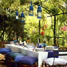 Lanterns, garden arch, color coordinating linens/table settings, pillow seats...love!