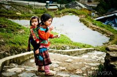 Vietnam, Sapa. Young Hmong girl carrying her little brother.