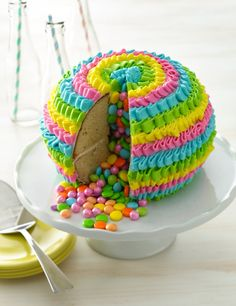 """Cakes don't get more fun than this! The first slice reveals  a cascade of coordinating candies, and the first bite will elicit nothing but """"yum""""s."""
