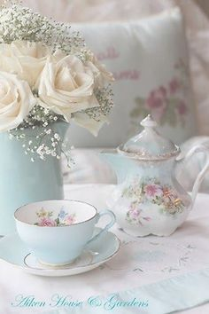 cup of tea by a beatufiul vase of white roses and babies breath <3