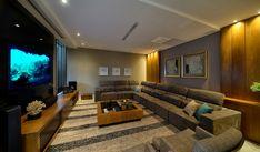 Home theater com  sofá em L, móveis e painel em carvalho e painel para tv em laca preta