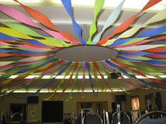 Party Prop~ Start with a hula-hoop and several rolls of crepe paper. Once you have them all attached to the hula-hoop, raise it into place and then twirl and attach all the end of streamers to the walls. You could also add some lights!