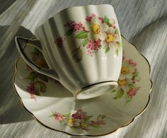 This tea cup and saucer set is by Victoria C&E of England and is made of bone china. It has soft white flowers with yellow centers that appear to be magnolias or daffodils, and pink flowers that look like lilacs. The background is more cream or ivory than white. There seems to be