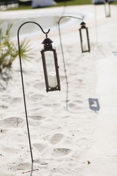 The shepherd's hook strikes again- this time with lanterns and white candles for a beachy-chic wedding.