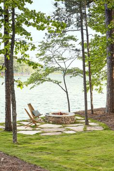 Large flagstone pieces in grass joints with a stacked stone fire pit. Backyard Patio by the Lake - A pair of iconic clean-lined Kentucky stick chairs adds a layer of sophistication to the natural stone fire pit—echoing the rustic. Diy Fire Pit, Fire Pit Backyard, Backyard Patio, Patio Stone, Flagstone Patio, Modern Backyard, Concrete Patio, Lake Landscaping, Landscaping Ideas