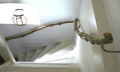 A reclaimed branch handrail in this Netherlands home lends an organic note to a simple, white stairwell.