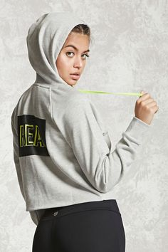 "An athletic French terry knit hoodie featuring a ""Real"" back graphic, hood with neon drawstrings, long raglan sleeves, and ribbed cuffs."