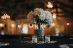 Beautiful wedding centerpiece for a navy and ivory wedding!  Love the simplicity and elegance of the white bouquet and candles.  And that navy blue linen--SO stunning! See more photos from this real wedding on the blog! #navyandivorywedding #navyandivoryweddingdecor #ivorytablecenterpiece #elegantweddingtablecenterpiece