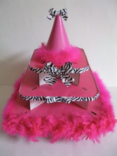 This adorable zebra print diva cupcake tower will WOW all the guests at your upcoming party!! The tower is three tiered and capable of holding up to three dozen cupcakes or a small cake and two dozen cupcakes. You can also put extra cupcakes around the base of the tower for a fun look. Bright, fun and funky pink feathers adorn the bottom tier of the tower, while black and white zebra print ribbon grace the top two tiers.