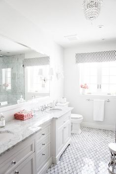 Stunning bathroom features a crisp white wall lined with a full length white vanity mirror illuminated by Robert Abbey The Muses Calliope 1 Light Wall Sconces situated over a white dual washstand topped with gray and white marble fitted with his and her sinks atop a Saltillo Imports Long Octagon Tile floor next to a faux stag head placed over the toilet next to a window dressed in a white and black geometric valance illuminated by a crystal chandelier.