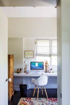 Escritorio doméstico con tabla flotante laqueada, una lámpara 'Tolomeo' y una silla 'Eiffel'.