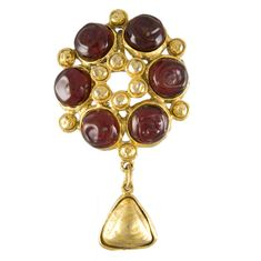 Chanel. This vintage brooch/pendant features six bezel set cranberry red poured glass stones set in a gold plated setting. Stamped and marked Chanel made in France.1980s