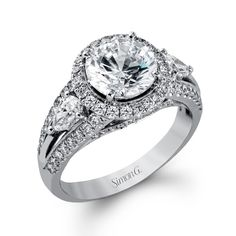 Brides.com: Three-Stone Engagement Rings. Style MR1503, 18K white gold ring with .63ctw round white diamonds and .51ctw pear-shaped side diamonds, $6,160, Simon G                                                                                                               See more Simon G engagement rings.