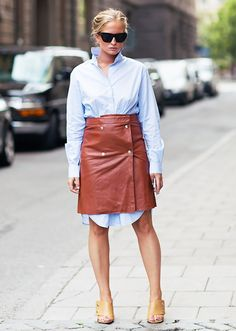 A shirtdress is worn with a leather skirt, mules, and rectangular sunglasses