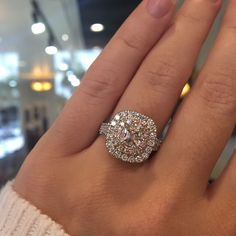 This Henri Daussi engagement ring features a 0.55ct Cushion cut center diamond that is framed in a perfect halo setting by pink diamonds and white diamond accents!
