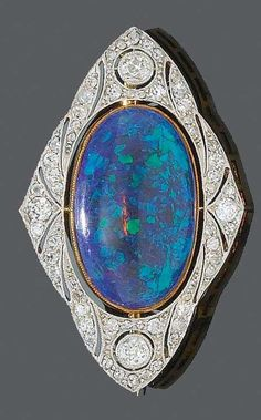 A BELLE EPOQUE OPAL AND DIAMOND BROOCH, CIRCA 1915. Set to the centre with one oval black opal cabochon weighing approximately 8.0 carats, within a pierced frame set with old-cut diamonds, mounted in platinum and gold. #BelleÉpoque #brooch #opalsaustralia