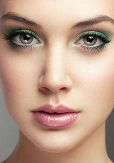 Delineado color verde metálico y labios rosa pálido brillante.