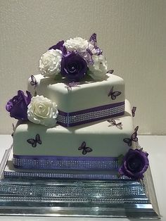 A 2 tier square wedding cake  in ivory , finished with purple and ivory roses and purple ribbon with diamonte trim