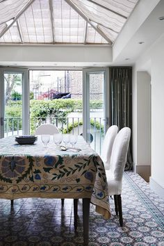 Across lies the conservatory dining room, with a tiled floor from Walton Ceramics.