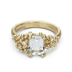 Ruth Tomlinson cocktail ring featuring an emerald cut aquamarine and white diamonds in 14ct yellow gold, handmade in our central London studio