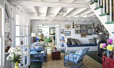 The long built-in bench in the sitting room is where people sit and talk on the only phone in the house. Sydney cushion fabric by Brunschwig & Fils. Walls throughout the house are painted in Glidden's Quiet Retreat, and the floors are in Benjamin Moore's Chrome Green.   - CountryLiving.com