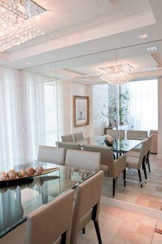 A parede revestida de espelho bisotê reflete e amplia a sala de jantar. Luminária plafon em cristais confere requinte à decoração do ambiente, que conta com mesa quadrada com tampo de vidro diamond translúcido e cadeiras em madeira laqueada e seda pura impermeabilizada na cor bege claro.