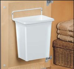 While looking for a space-saving trash, I found this door-mounted kitchen garbage can on Amazon.com and think it would work great for under a bathroom sink as well.