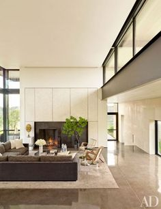 In the living room, the steel fireplace surround is framed in eggshell-veneer panels by Chapeau Design.
