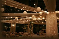 A simple and elegant way to accent any venue. This specific wedding reception used a design that incorporated ivory fabric, twinkle lights and tulle to create a swag effect across the ceiling, accented by ivory paper lanterns and larger twinkle lights strewn across the room. A design such as this one can help to make a larger venue more intimate and it also creates a soft and warm ambiance for you and your guests as you enjoy your evening.