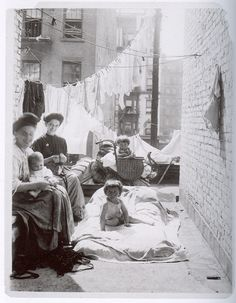Enjoy the morning on the roof. Lots of interesting stuff going on here. Babies on roofs, tenement living, working class women's clothing at home, are they knitting?