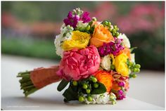 Let's talk bouquet: Vibrant, bold, festive--pink peonies, orange roses, magenta snapdragons and an orange collar. This bride went for it and it so works! // Venue: Wedgewood at David Girard Vineyards | Sunflower Field Photography