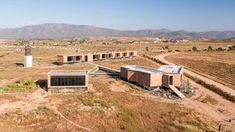 Mexican firm Santos Bolivar Architects has given the red-block buildings that form this inn reflective bottoms to make it seem like they are floating above the arid landscape in Valle de Guadalupe. Guadalupe Valley, Ensenada Baja California, Natural Ecosystem, Wooden Terrace, Soil Improvement, Public, Rammed Earth, Geodesic Dome, Space Gallery