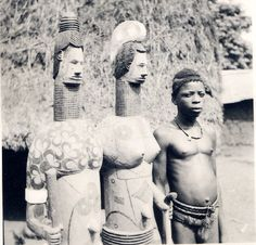 Nigeria, half-length portrait of young adult male standing beside pair of life-size wooden [?] figures on stand. Figures appear to represent adults [male and female?], wearing belts or loin-cloths, neck-ornaments, painted torsos, elaborate hair-styles. Male wearing loin-cloth, neck-ornament. Settlement setting, section-view of thatched-roof building in background. Medium: Gelatin silver print.