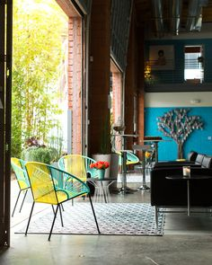 Eclectic Decor - An indoor-outdoor meeting area with bamboo plantings at Jessica Alba's Honest Company office