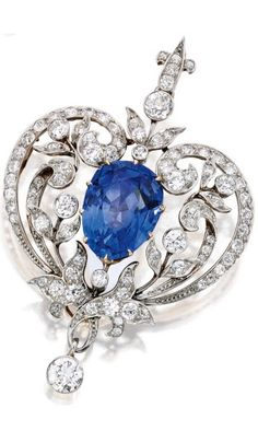 Platinum-Topped Gold, Sapphire and Diamond Pendant-Brooch, Marcus & Co. Centred by a pear-shaped sapphire weighing approximately 15.00 carats, within scrollwork surrounds set with old European-cut diamonds weighing approximately 4.50 carats, signed Marcus & Co., circa 1900.