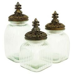 "Stow cotton balls in your powder room or peppermints on your console table with these ribbed glass jars, showcasing fleur-de-lis finial lids.  Product: Small, medium and large jar setConstruction Material: GlassColor: Brown and goldFeatures:  RibbedFleur-de-lis finial lidsDimensions: Large: 14.5"" H x 6.5"" W x 6.5"" DMedium: 12"" H x 6.5"" W x 6.5"" DSmall: 11"" H x 6.5"" W x 6.5"" D"