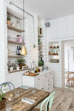 Love the gentle, cool feel of the white walls and bright light. Great texture contrast between the exposed brick and wooden cl added walls.