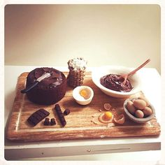 Chocolate Sponge Cake baking set. Includes a handmade cooking board, flour basket, bowl of 5 eggs and one single egg shell and yolk, Cake batter bowl & wooden spoon, miniature mixing bowl with an egg and flour, sponge cake and icing knife and a tiny bar of chocolate broken into pieces. The set is glued to the cooking board to ensure the effect is kept just the way a tiny person would have left it after licking the batter bowl! This set can be customised in any way you would like, just send…