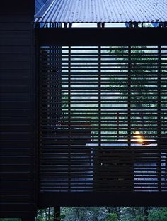 A Rustic-Modern Cabin Inspired by Japanese Bungalows and Shou Sugi Ban - Photo 6 of 12 - Pine slats, which were intentionally spaced unevenly, partially enclose the side deck. Outdoor areas add nearly 300 square feet to the cabin, whose interior measures about 1,000 square feet.