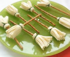 """Witches Cheese Brooms - All you need for these scary treats are: 12 Slices of Cheese, 12 Pretzel Sticks,  12 Fresh Chives  1. - Fold the slice of cheese in half and with the help of scissors cutt the fringes for the broom. Two. - Roll with the """"fringe"""" down using the stick snack as broom shaft. Three. - And finally to keep the cheese near the snack uses a chive herb and tie"""